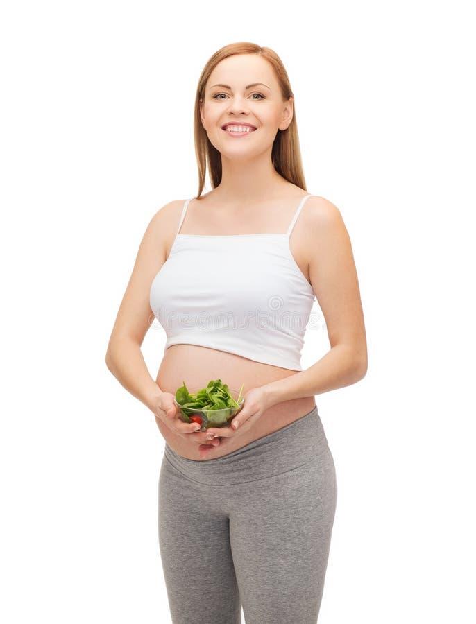 Gelukkige toekomstige moeder met kom salade stock afbeeldingen