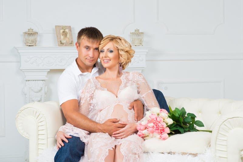 Gelukkige toekomstige vader met mooie leuke zwangere vrouwenzitting op bank met bloemen royalty-vrije stock afbeelding