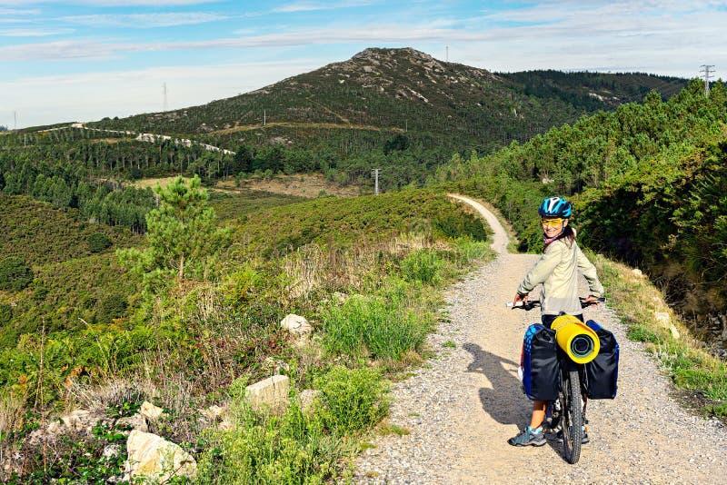 Gelukkige toeristenfietser op steenachtige heuvelige weg royalty-vrije stock fotografie