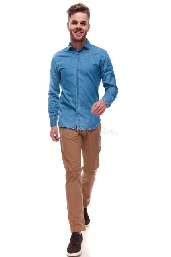Gelukkige toevallige mens die met blauw overhemd vooruit lopen royalty-vrije stock foto's