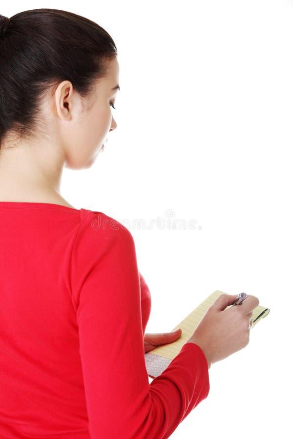 Gelukkige toevallige vrouw die op een stuk van document schrijven. Achtermening. stock foto's