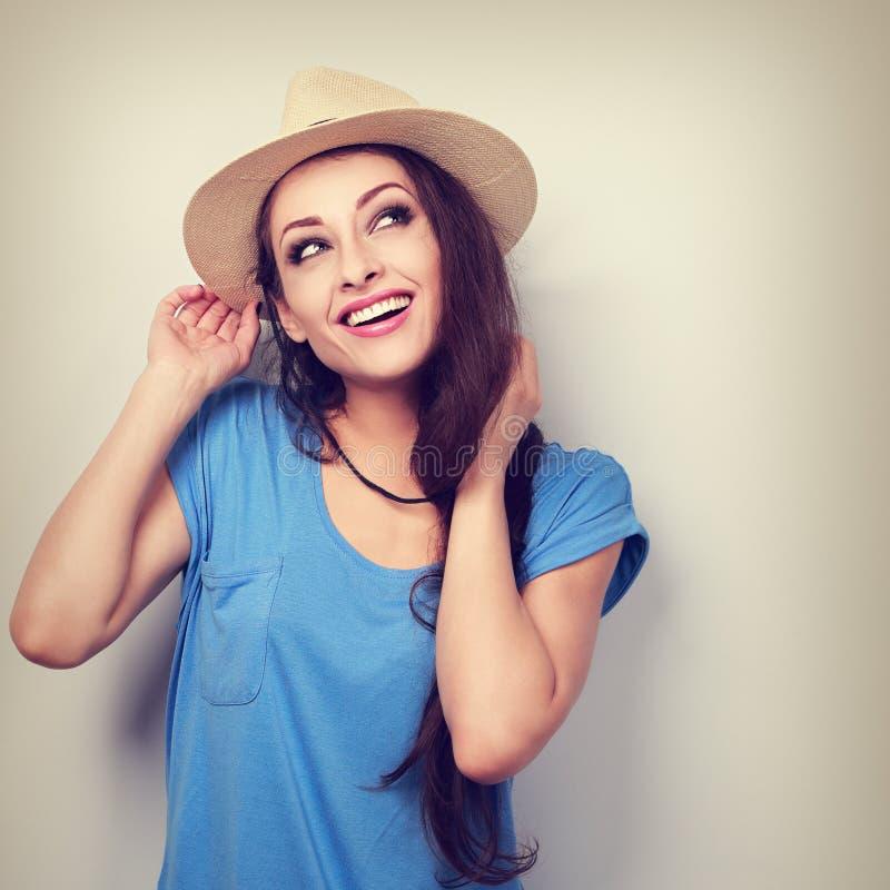 Gelukkige toothy glimlachende vrouw in en hoed die omhoog denken eruit zien gestemd royalty-vrije stock fotografie