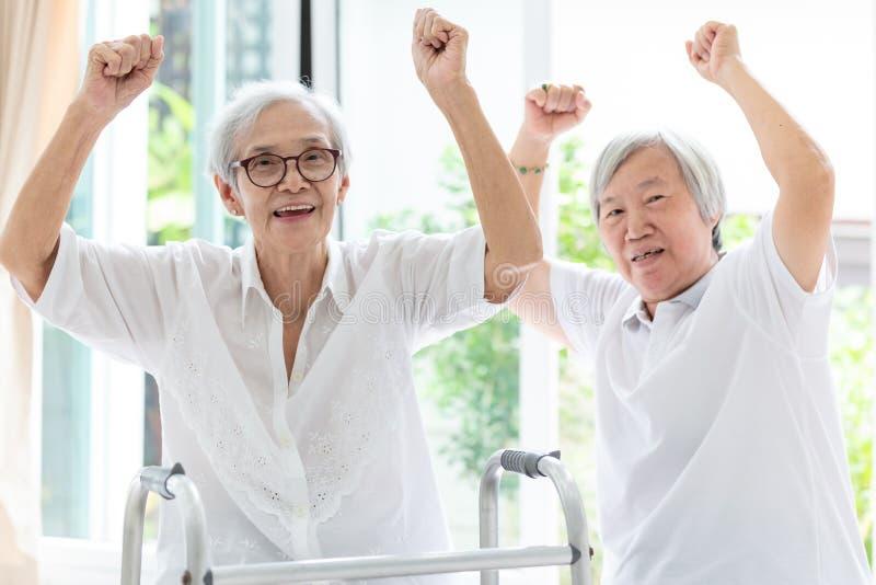 Gelukkige twee Aziatische hogere vrouwen vuist en hurrah, tijd die samen, vrienden van, en bejaarde of zuster opheffen die lachen stock foto's