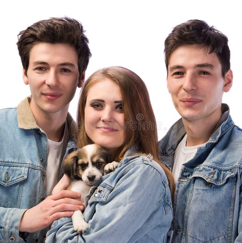 Gelukkige twee jonge mannen en vrouw met een hond royalty-vrije stock afbeeldingen