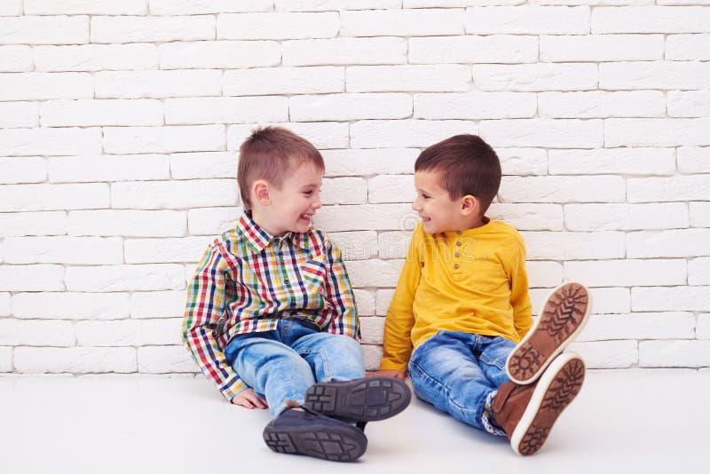 Gelukkige twee kleine jongens die op vloer zitten en bij elkaar glimlachen royalty-vrije stock foto's