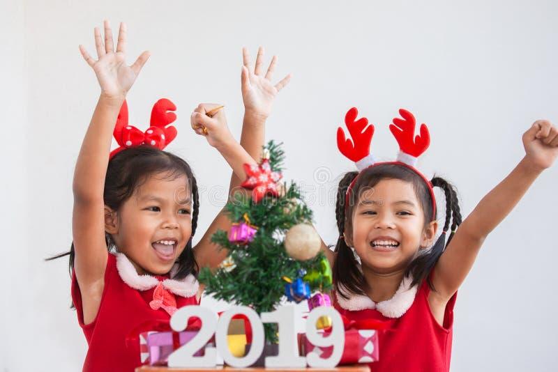 Gelukkige twee leuke Aziatische kindmeisjes met nummer 2019 stock afbeeldingen