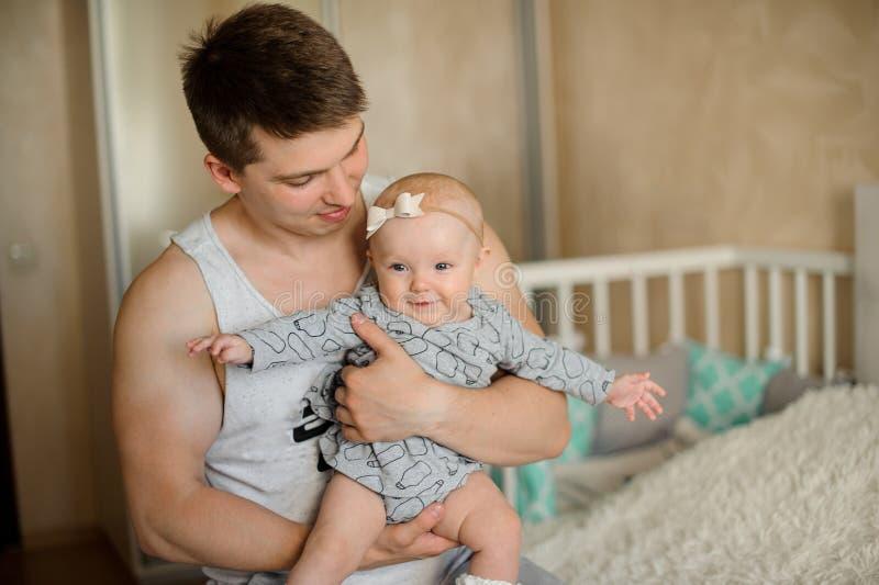 Gelukkige vader die een pasgeboren babymeisje in zijn wapens houdt royalty-vrije stock afbeelding