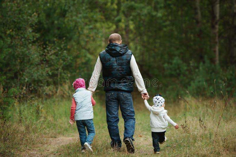Gelukkige vader die twee kleine daughers houden royalty-vrije stock afbeeldingen