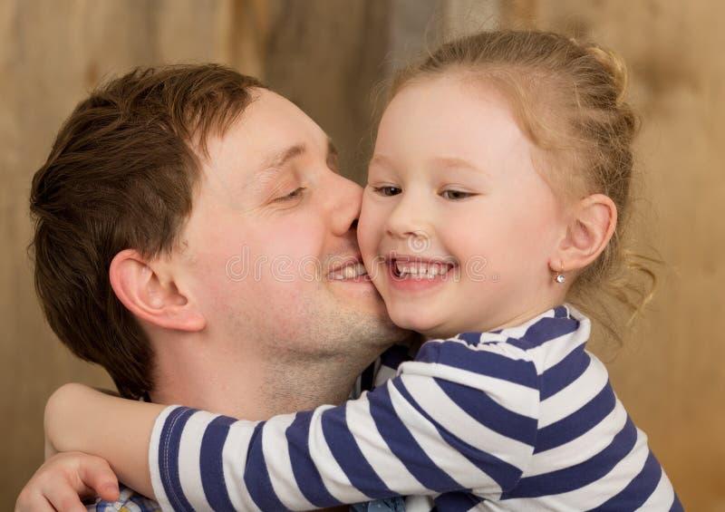 Gelukkige vader die weinig dochter kussen stock foto's