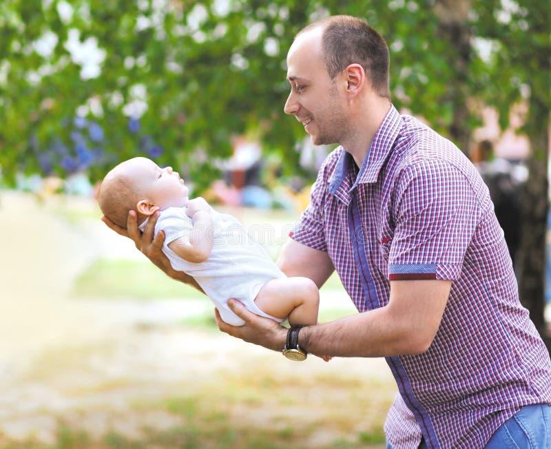 Gelukkige vader die weinig pasgeboren baby houden stock afbeelding