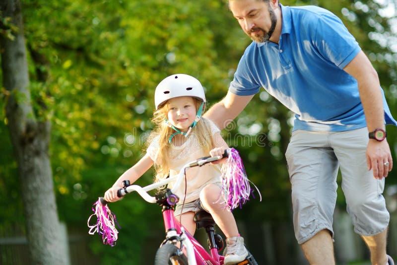 Gelukkige vader die zijn kleine dochter onderwijzen om een fiets te berijden Kind die een fiets leren te berijden stock foto's