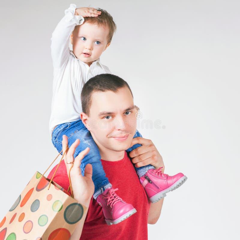 Gelukkige vader en de grappige zakken van de babyholding met aankopen royalty-vrije stock afbeeldingen