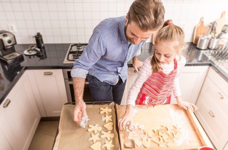 Gelukkige vader en dochter die koekjes in kitch voorbereiden te bakken stock foto