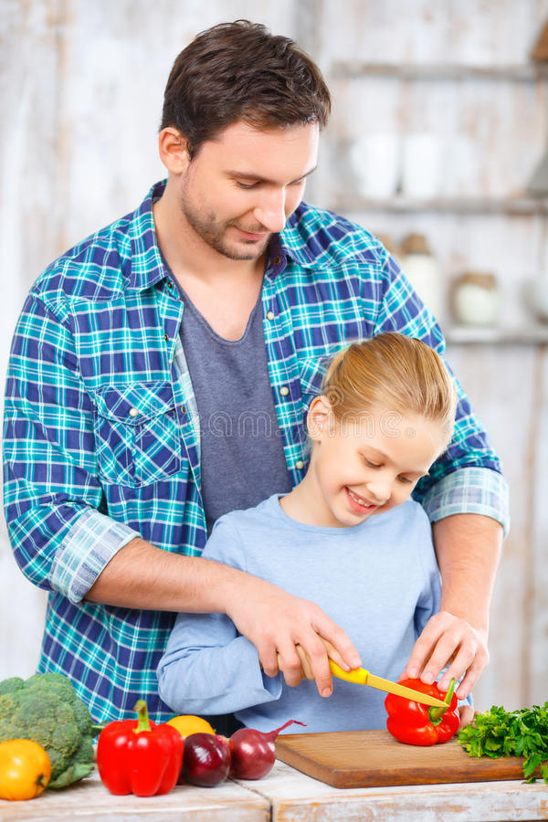 Gelukkige vader en dochter die samen koken stock foto