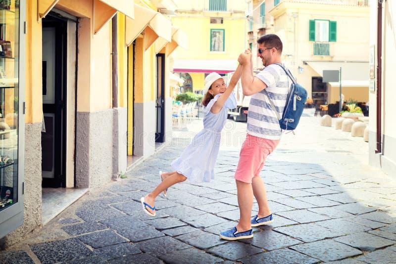 Gelukkige vader en dochter het besteden tijd die samen pret op stadsstraten hebben, glimlachend papa en meisje speelring rond ros royalty-vrije stock afbeelding