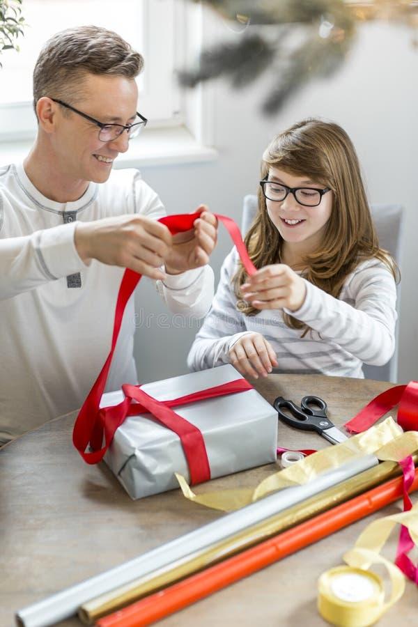 Gelukkige vader en dochter het verpakken thuis aanwezige Kerstmis stock fotografie