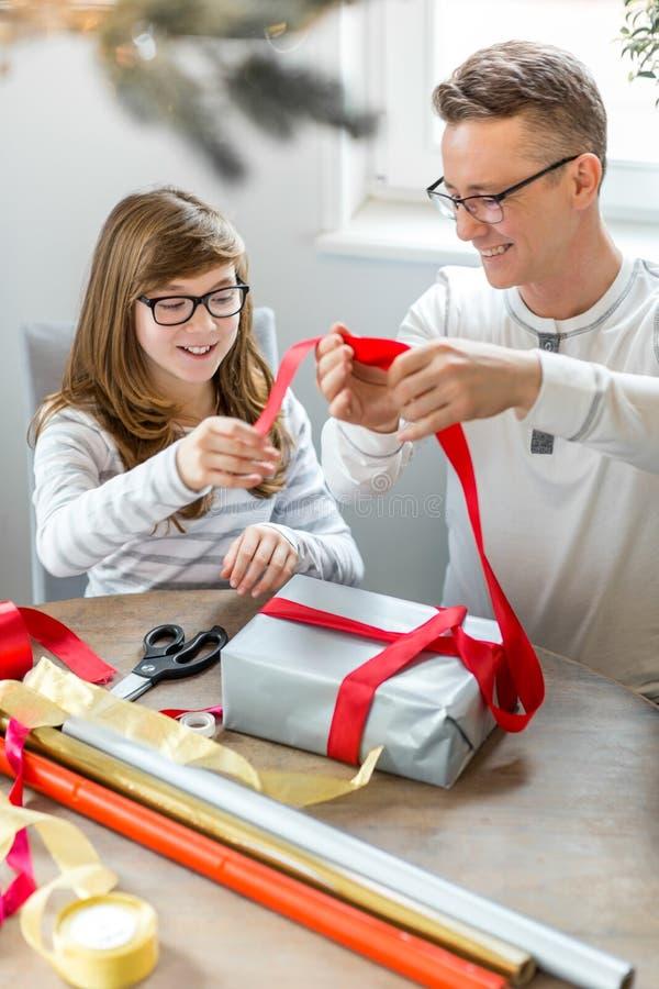 Gelukkige vader en dochter het verpakken thuis aanwezige Kerstmis royalty-vrije stock foto