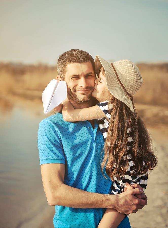 Gelukkige vader en dochter op het strand Het Concept van de vader` s Dag stock foto