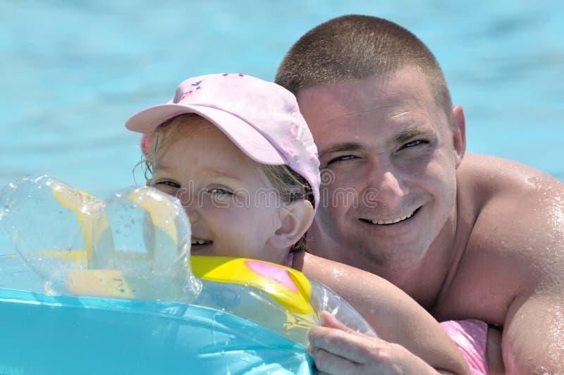 Gelukkige vader en dochter in pool stock afbeelding