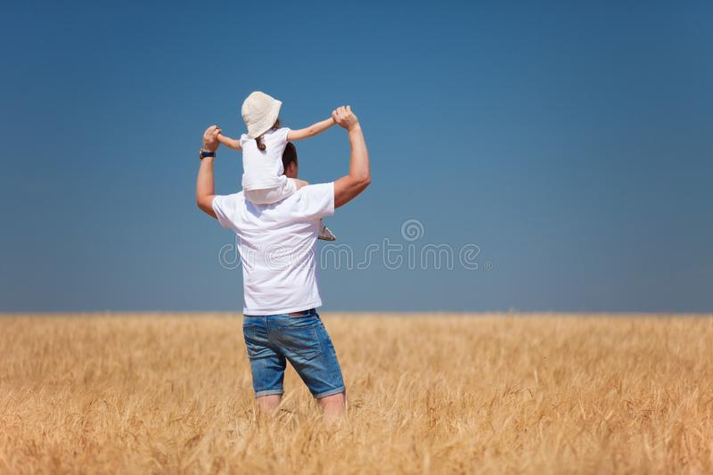 Gelukkige vader en dochtergang op het de zomergebied Aardschoonheid, blauw hemel en gebied met gouden tarwe Openlucht levensstijl stock afbeelding