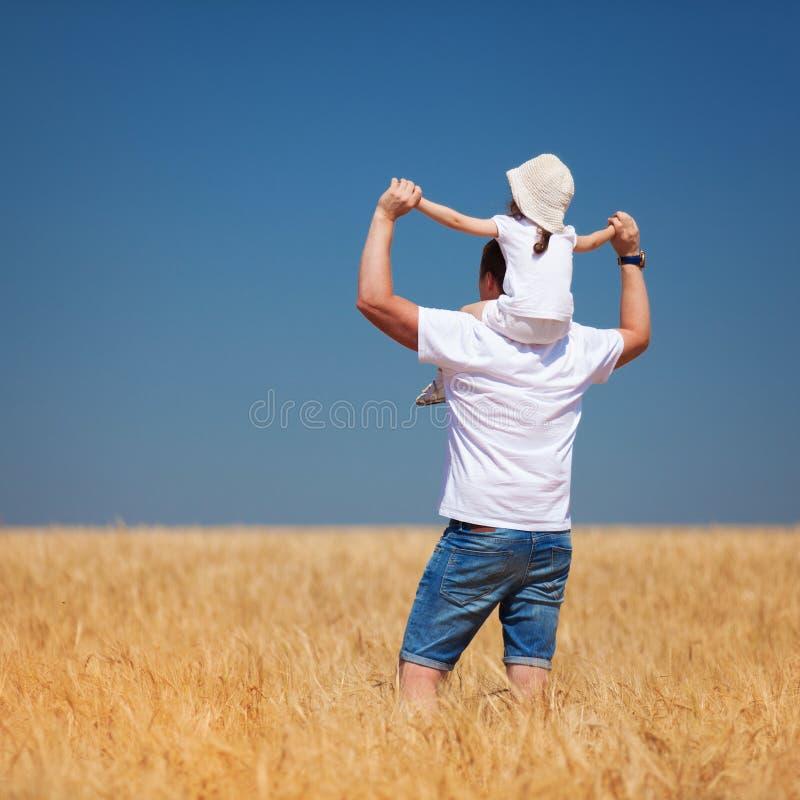 Gelukkige vader en dochtergang op het de zomergebied Aardschoonheid, blauw hemel en gebied met gouden tarwe Openlucht levensstijl stock foto's