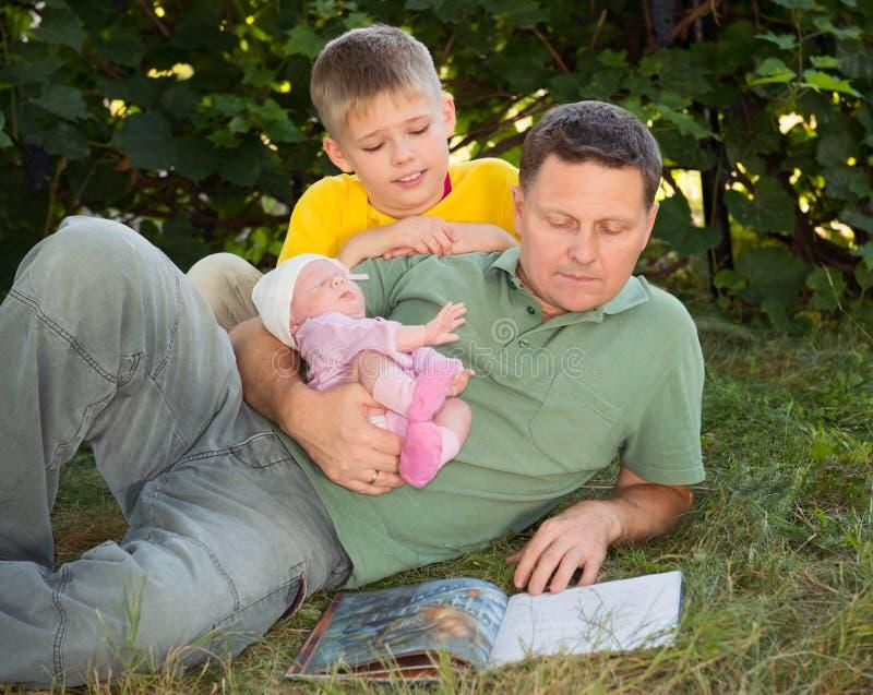 Gelukkige vader en kinderen die boek op het gazon in de tuin lezen stock foto