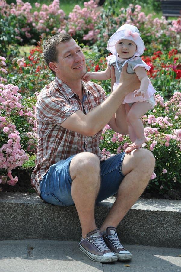 Gelukkige vader en leuke babydochter in het park stock foto