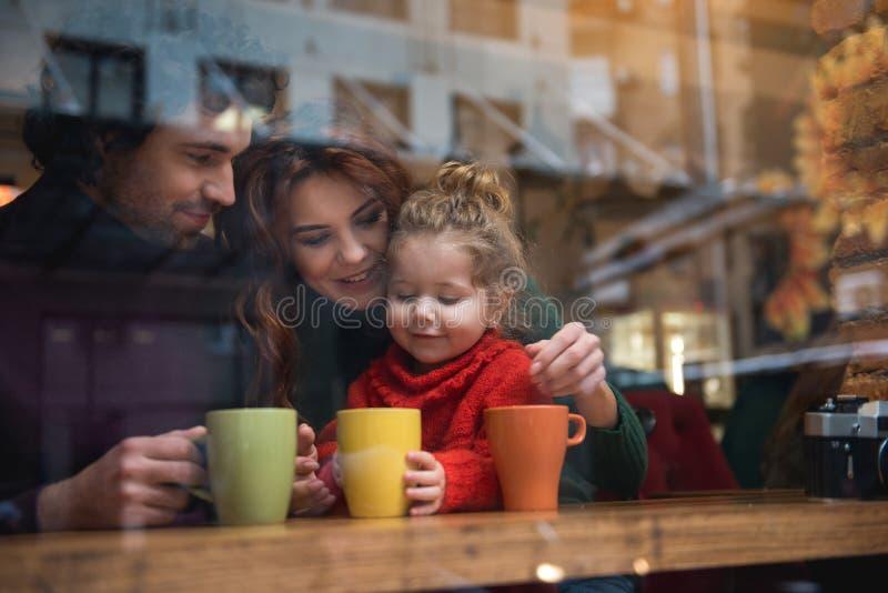 Gelukkige vader en moeder met dochter in koffie stock afbeeldingen