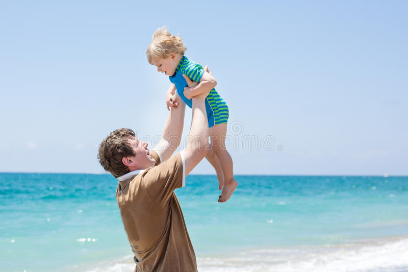 Gelukkige vader en weinig babyzoon die pret hebben bij strandvakantie royalty-vrije stock fotografie