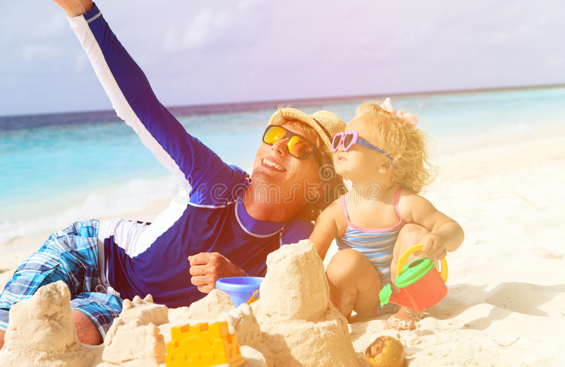 Gelukkige vader en weinig dochter bij strand het maken stock foto