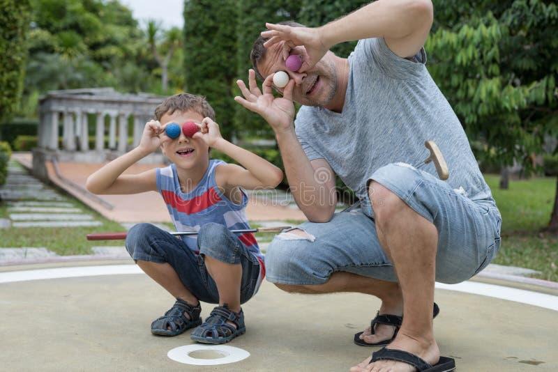 Gelukkige vader en weinig zoon die minigolf spelen royalty-vrije stock afbeelding