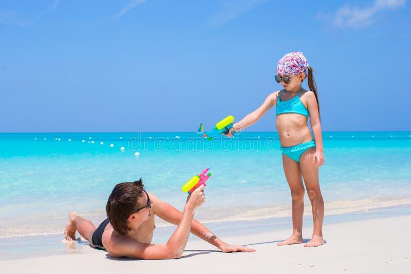 Gelukkige vader en zijn aanbiddelijke kleine dochter bij tropisch strand die pret hebben stock afbeelding