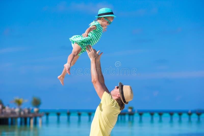 Gelukkige vader en zijn aanbiddelijke kleine dochter bij tropisch strand die pret hebben royalty-vrije stock foto
