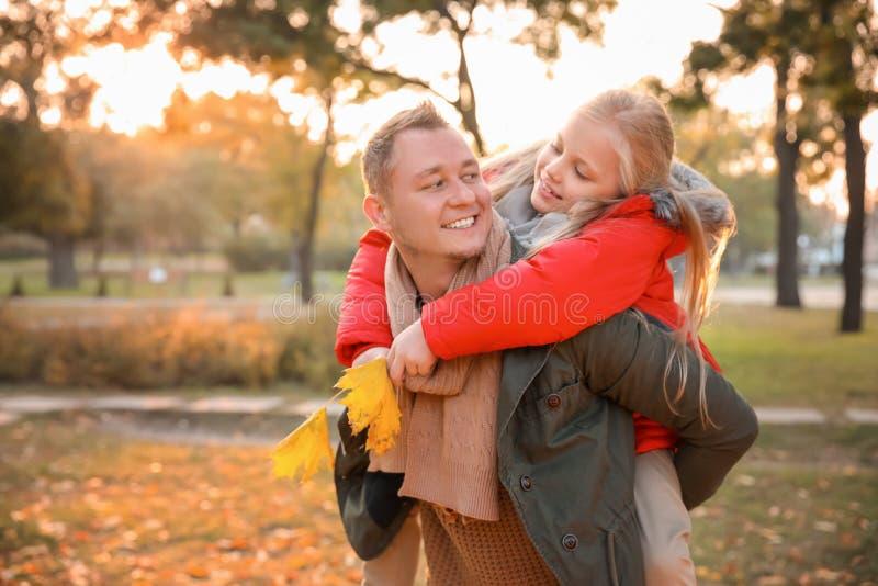 Gelukkige vader en zijn kleine dochter in de herfstpark stock fotografie