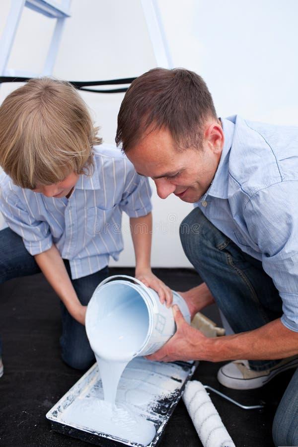 Gelukkige vader en zijn zoon die verf voorbereiden royalty-vrije stock foto