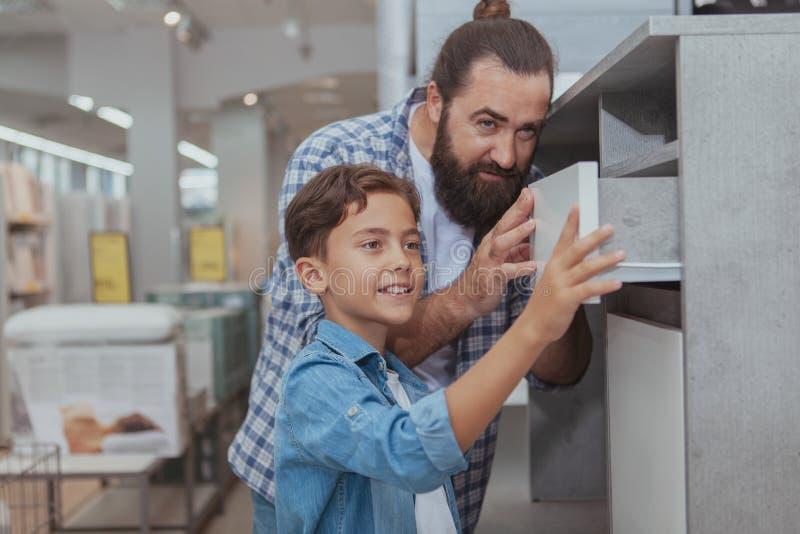 Gelukkige vader en zoon die bij warenhuis winkelen stock fotografie