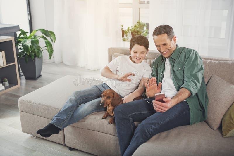 Gelukkige vader en zoon die Internet-mededeling hebben thuis stock afbeeldingen