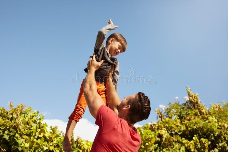 Gelukkige vader en zoon die pret hebben in openlucht stock afbeelding