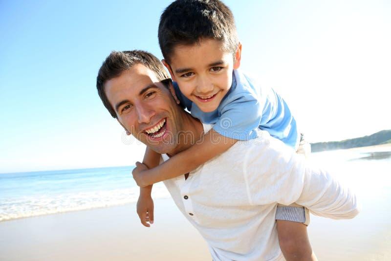 Gelukkige vader en zoon die pret op het strand hebben stock afbeeldingen