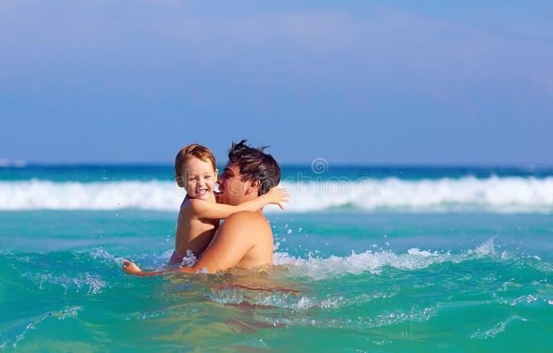 Gelukkige vader en zoon die pret in watergolven hebben royalty-vrije stock foto