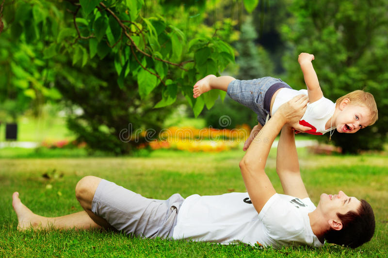 Gelukkige vader en zoon die samen het hebben van pret in groene su spelen stock afbeeldingen