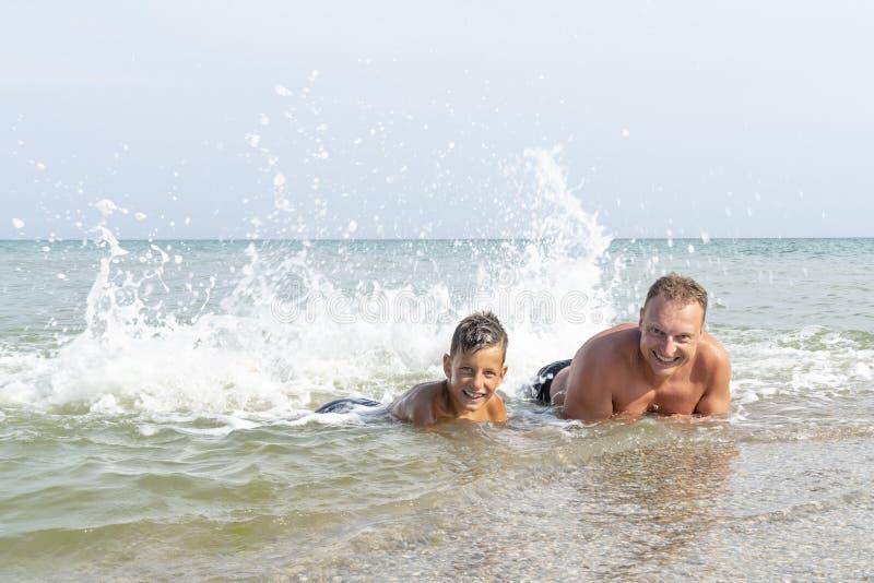 Gelukkige vader en zoon die strand van tijd op de zomervakantie genieten in een zonnige dag royalty-vrije stock foto's