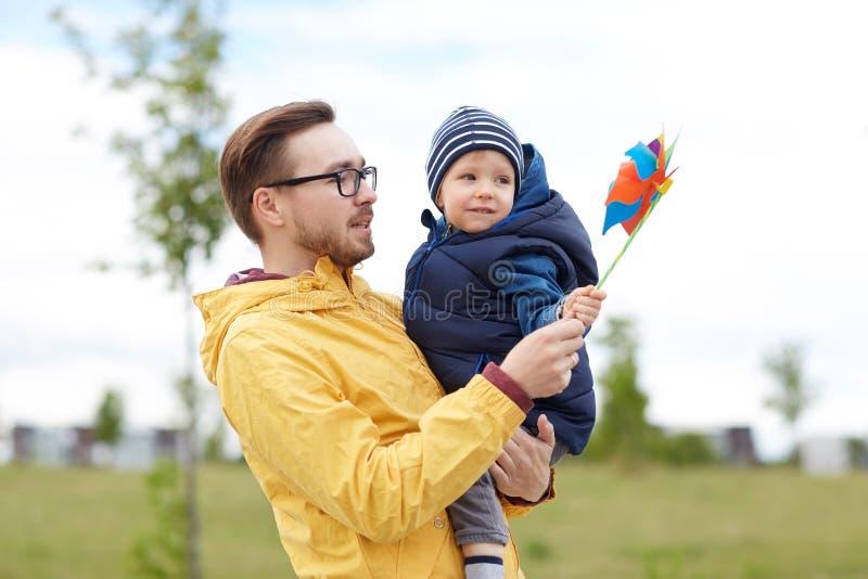 Gelukkige vader en zoon met vuurradstuk speelgoed in openlucht royalty-vrije stock fotografie