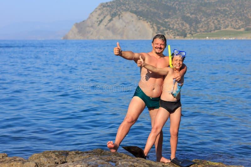 Gelukkige vader en zoon op het overzeese strand stock afbeeldingen