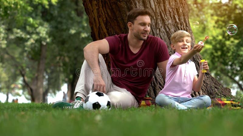 Gelukkige vader en zoons blazende bellen, die pret hebben die samen, vrije tijd doorbrengen royalty-vrije stock foto's