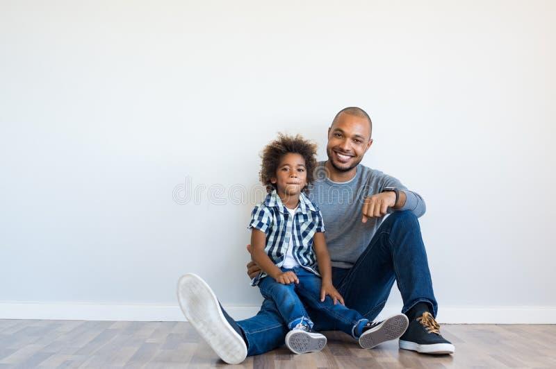 Gelukkige vader en zoonszitting stock foto's
