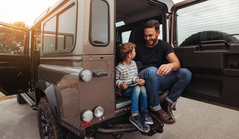 Gelukkige vader en zoonszitting bij de rug van de auto stock foto