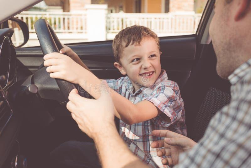 Gelukkige vader en zoonszitting in de auto in de dagtijd stock foto's