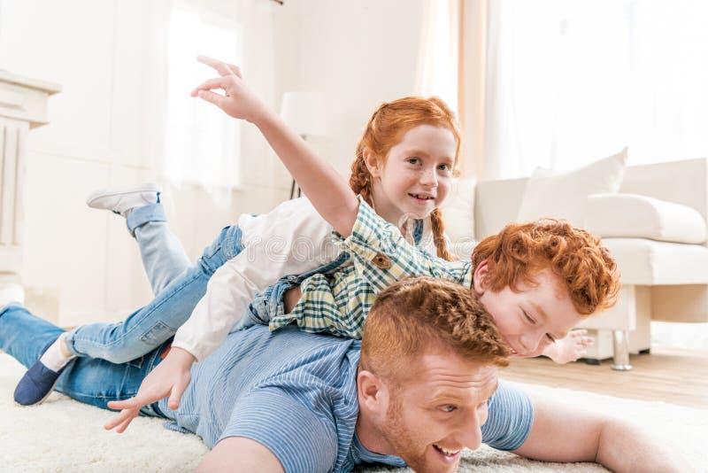 Gelukkige vader met aanbiddelijke roodharigekinderen die en pret samen op vloer spelen hebben stock foto