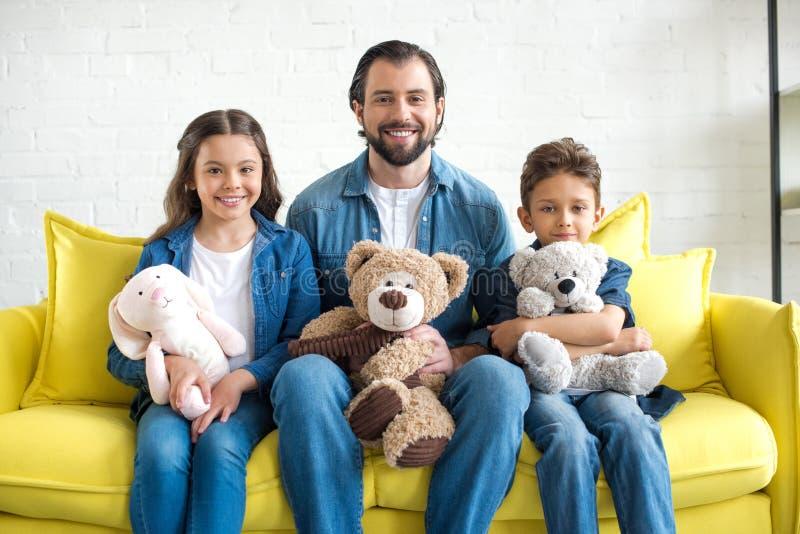 gelukkige vader met twee aanbiddelijke jonge geitjes die speelgoed houden en bij camera glimlachen royalty-vrije stock foto